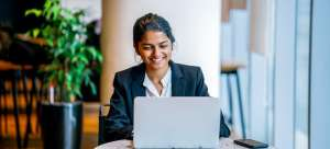 Smiling woman in a business suit sitting at a table with her laptop and smart phone