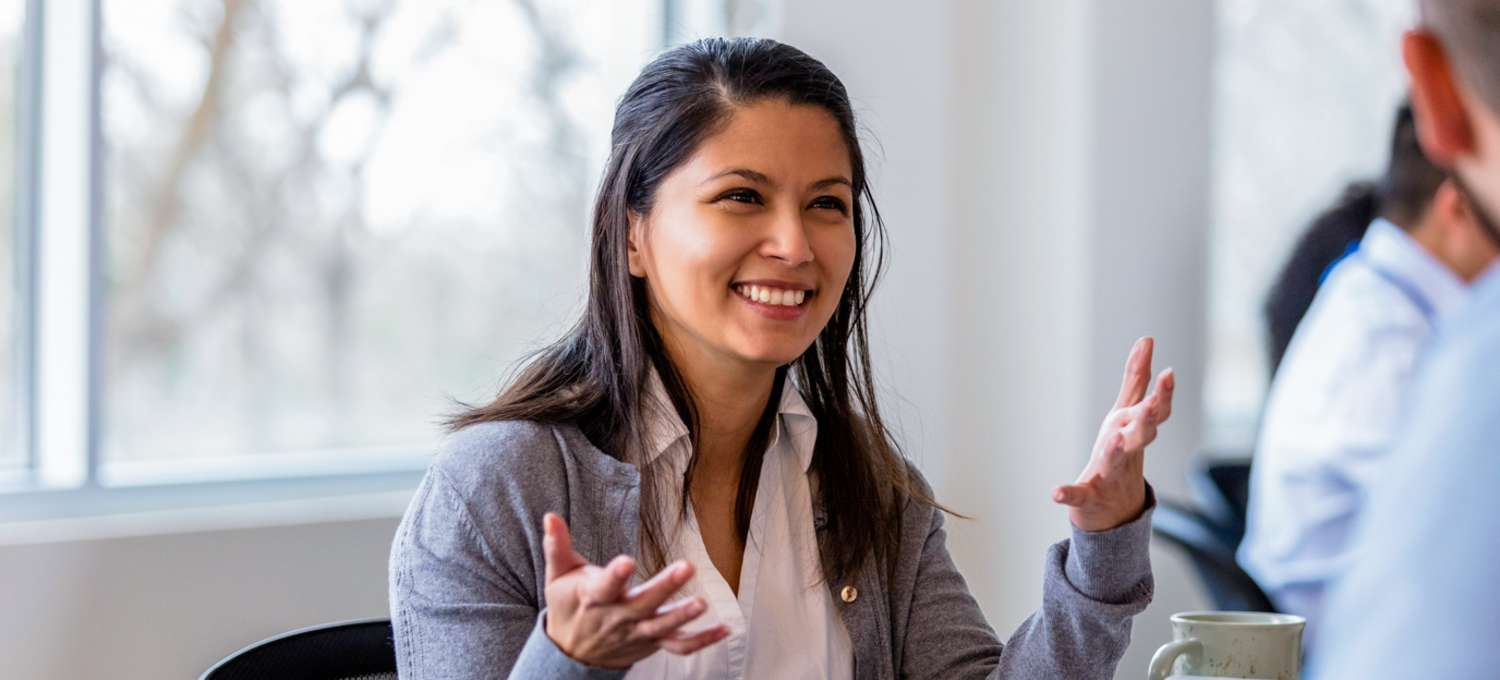 A young woman working in healthcare administration speaking animatedly with her colleague