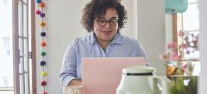 A graphic designer sits at a table with her pink laptop in a brightly lit room