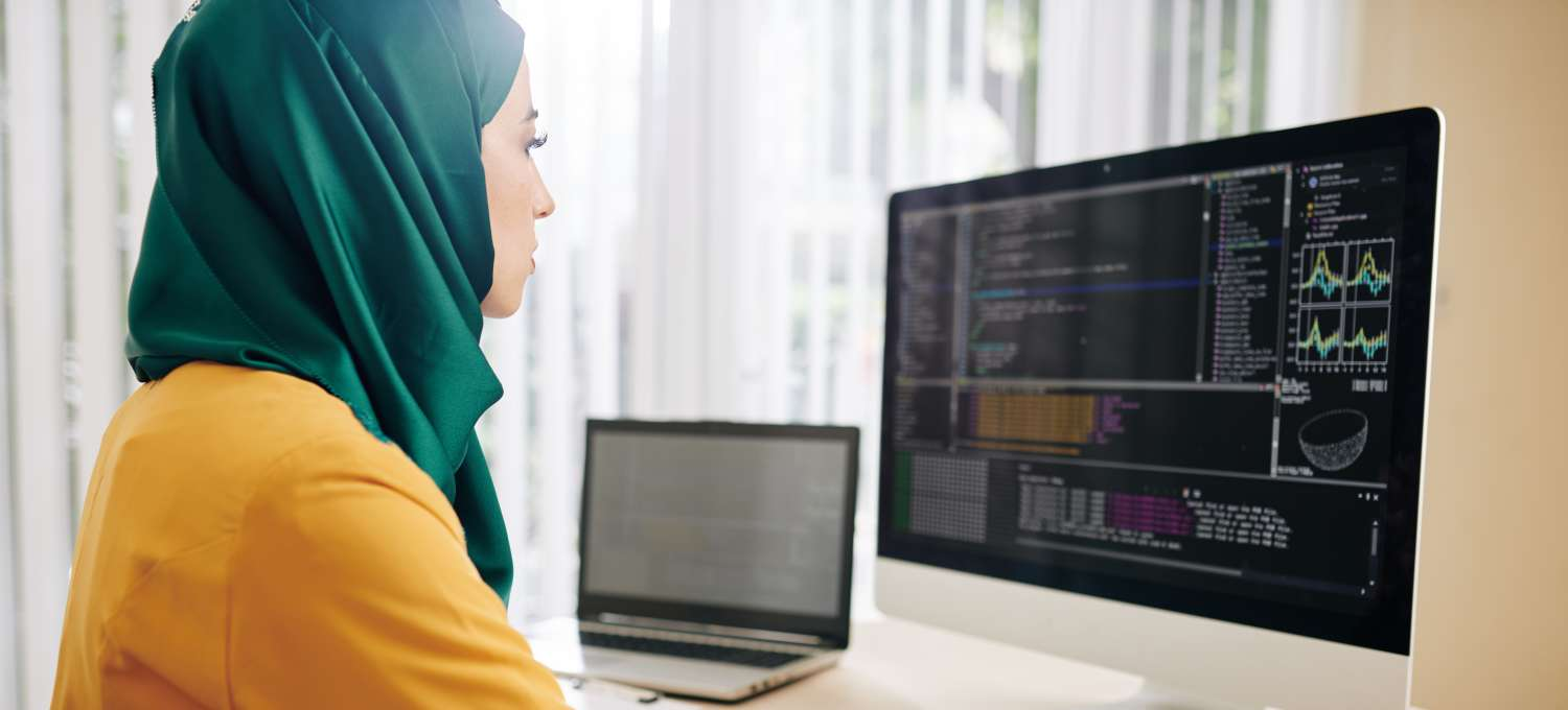 Female data engineer sits in front of a dual computer screen looking at data visualizations and writing in a notebook