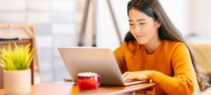 A cloud engineer wearing a bright orange sweater works at her laptop with a hot beverage in a bright office or cafe.