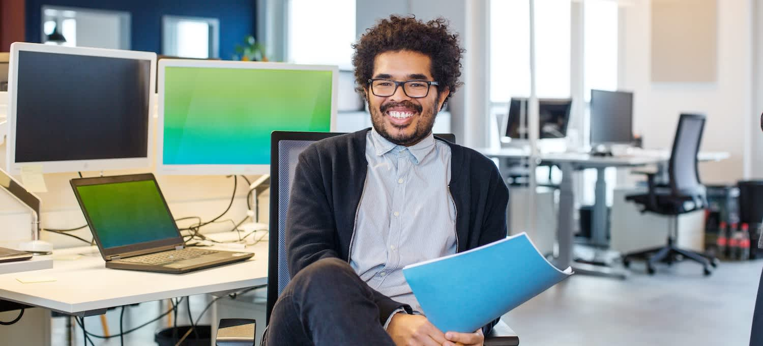 A man with glasses and a blue folder sits at a cybersecurity workstation with three computer screens.