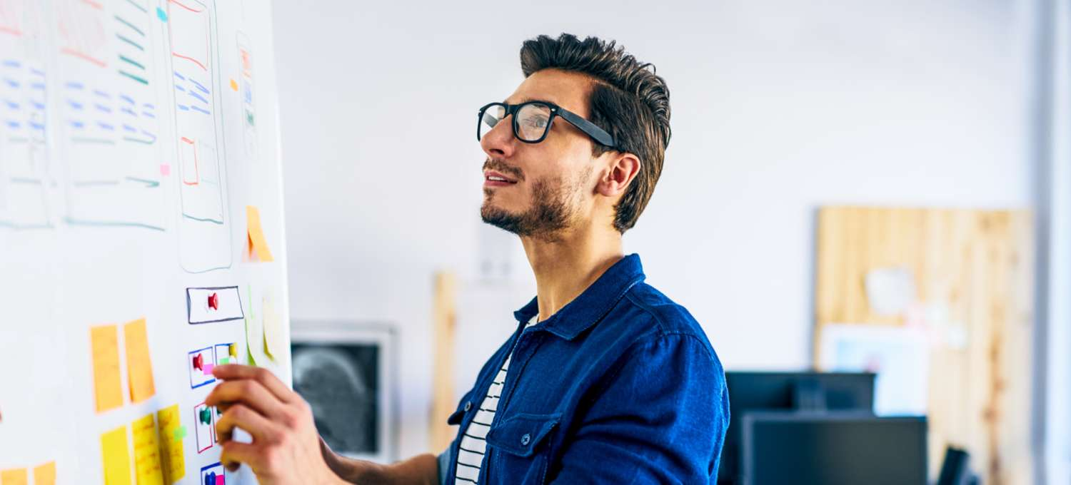 Male UX designer in glasses and a blue shirt drawing a wireframe on a whiteboard