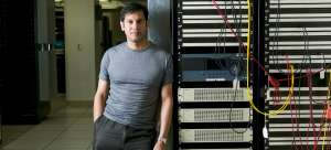 A digital forensic investigator leans against a computer server in a data center. He's wearing a grey t-shirt and dark grey pants.