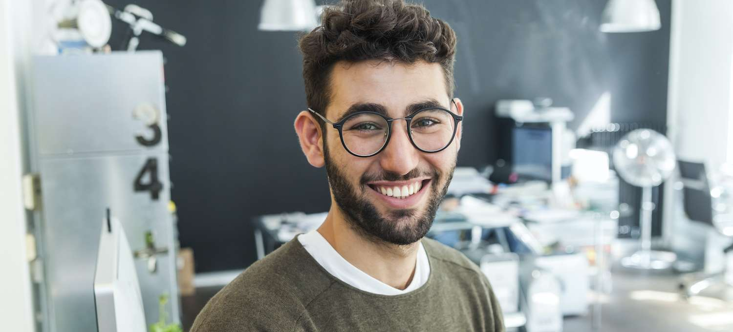 Smiling man in a sweater and glasses standing in front of his desk