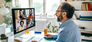 Man with a beard and glasses on a Zoom call with four colleagues