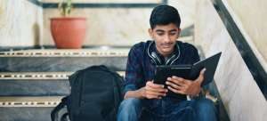 A male college student sits on steps and looks at his tablet. His backpack sits next to him.