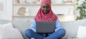 Woman wearing a pink al-amira sits on a grey sofa working on a laptop computer