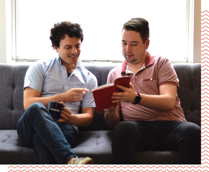 2 people looking at a book on a couch