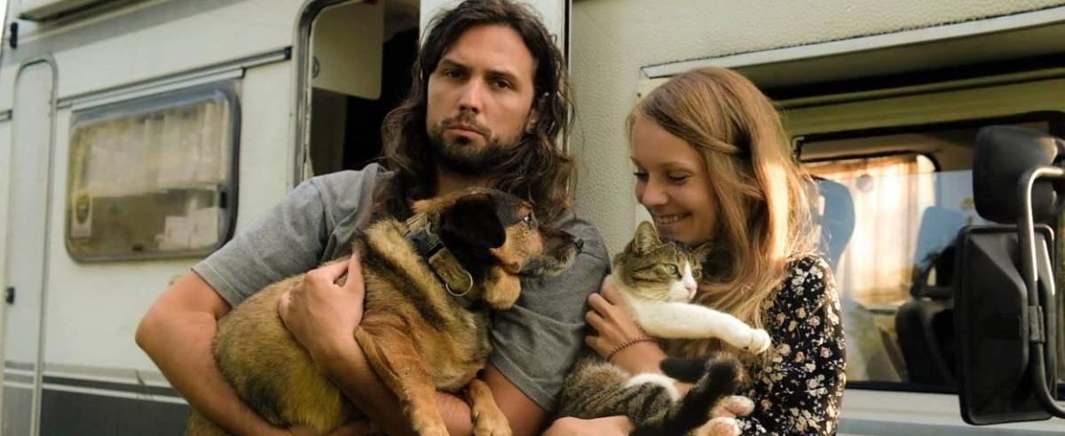 Ludzie z psem i kotem przy kamperze