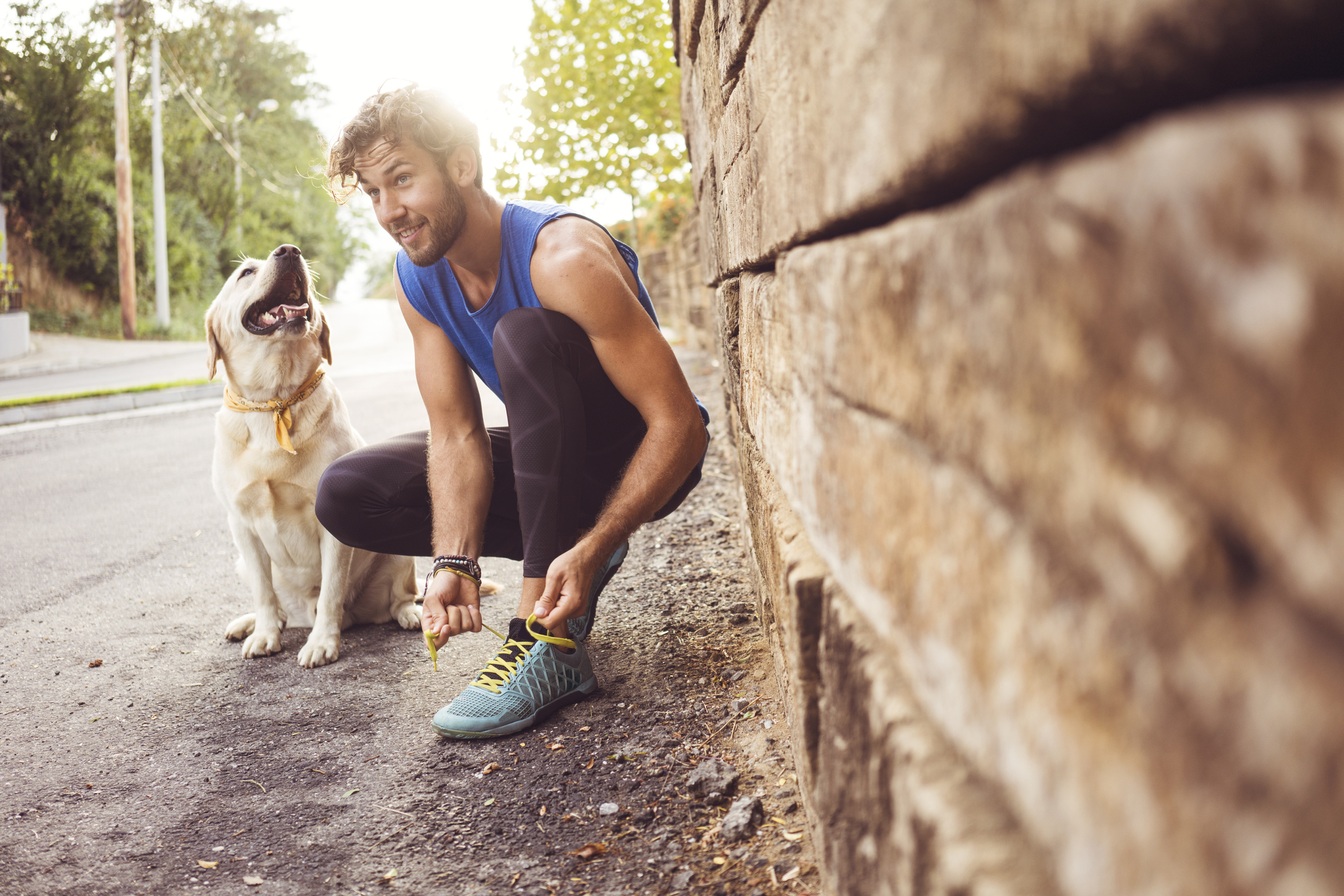 Man tying up his shoelaces before leaving for a run with his dog