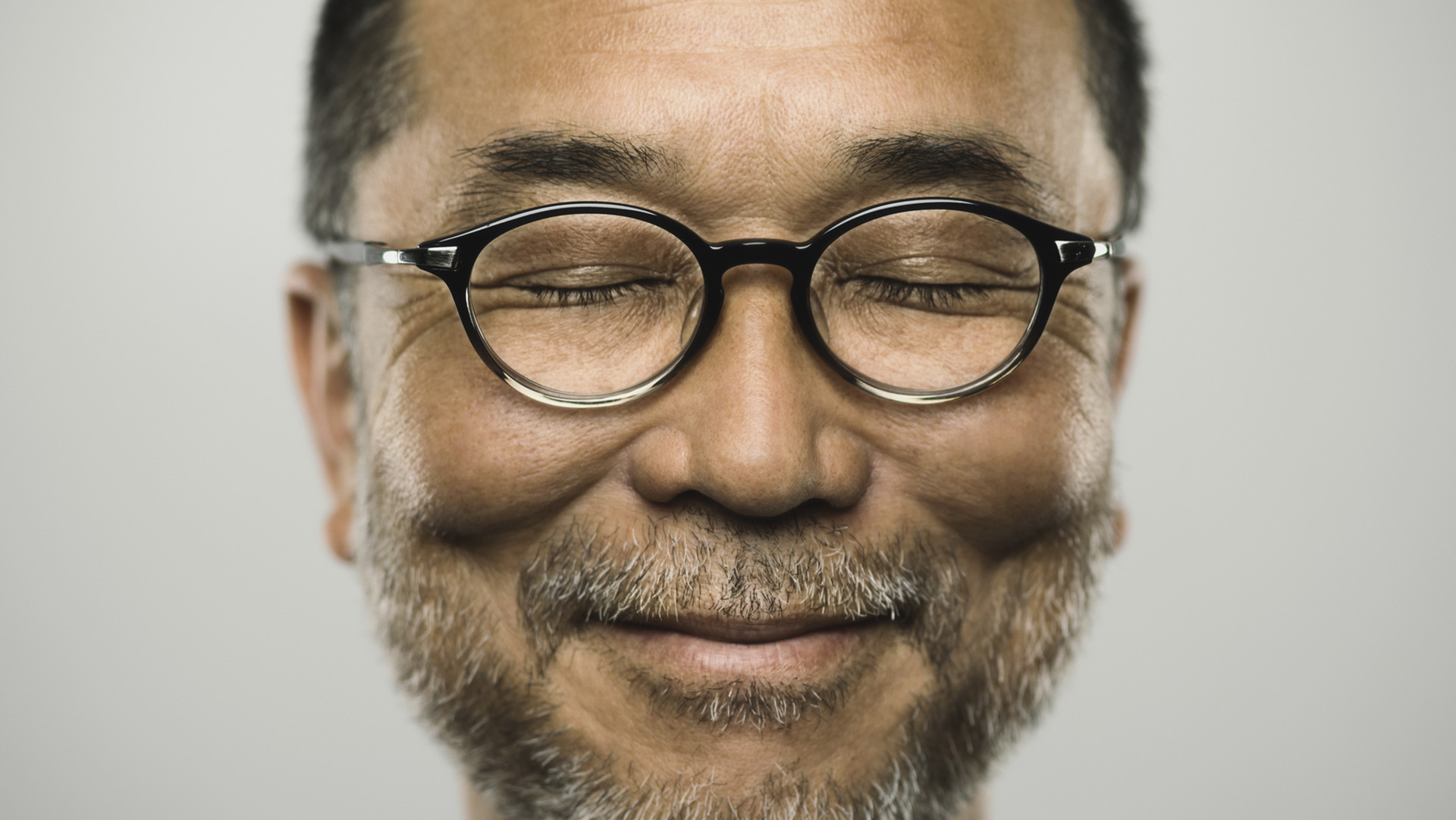 Studio portrait of a japanese mature man looking at camera with relaxed expression. The man has around 50 years and has glasses, short hair and a short grey beard. Vertical colour image from a medium format digital camera.
