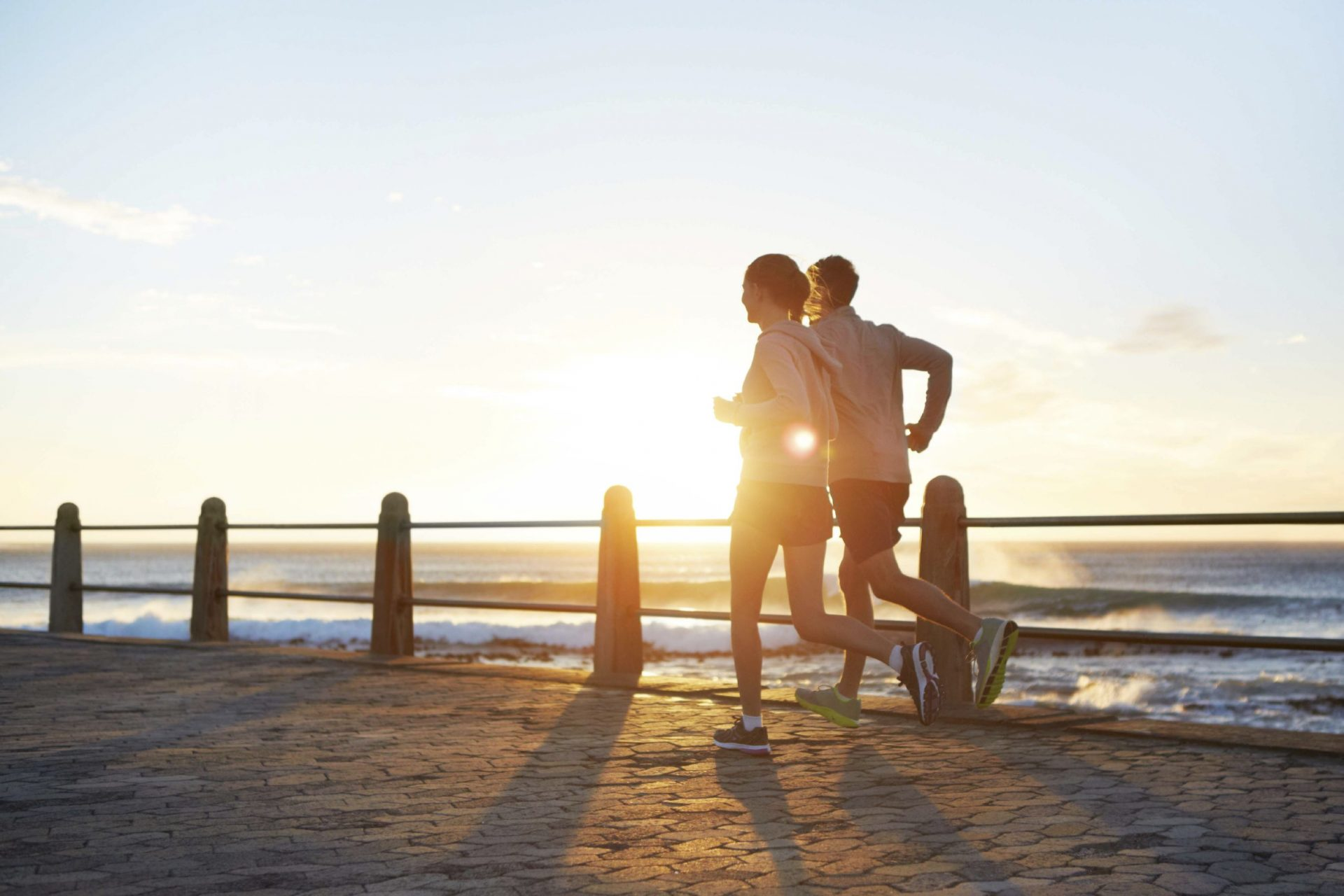 A young couple jogging on the promenade at sunset