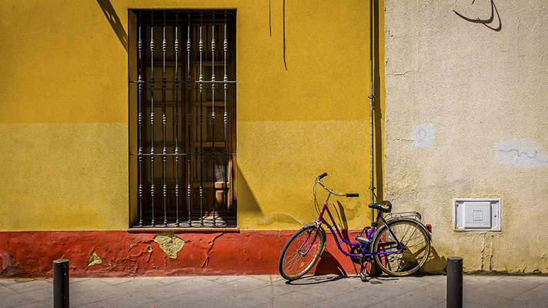 Seville, Spain – May 28, 2015: A Seville street door with metal cage cover and an adjacent parked bicycle on a bright sunny day