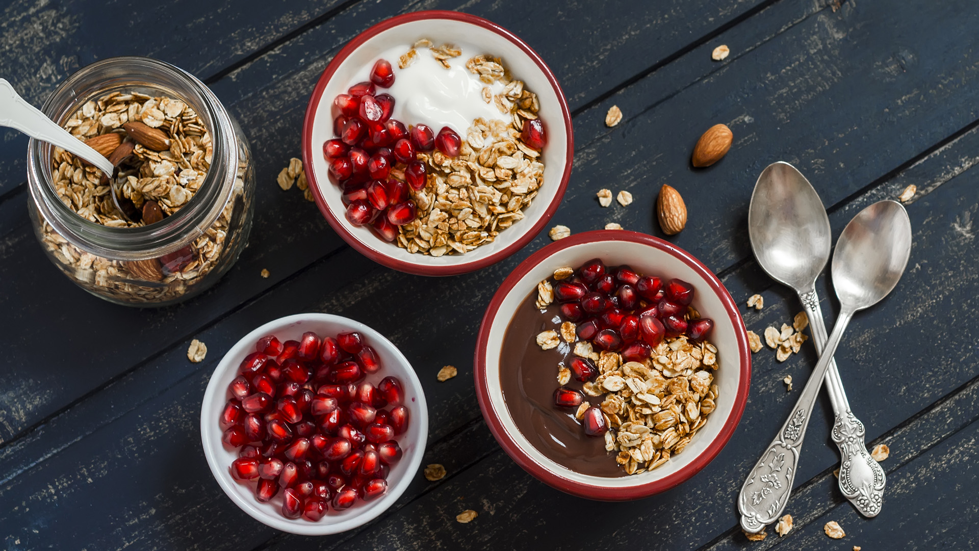 Healthy Breakfast - yogurt with homemade granola and pomegranate on a dark wooden board.