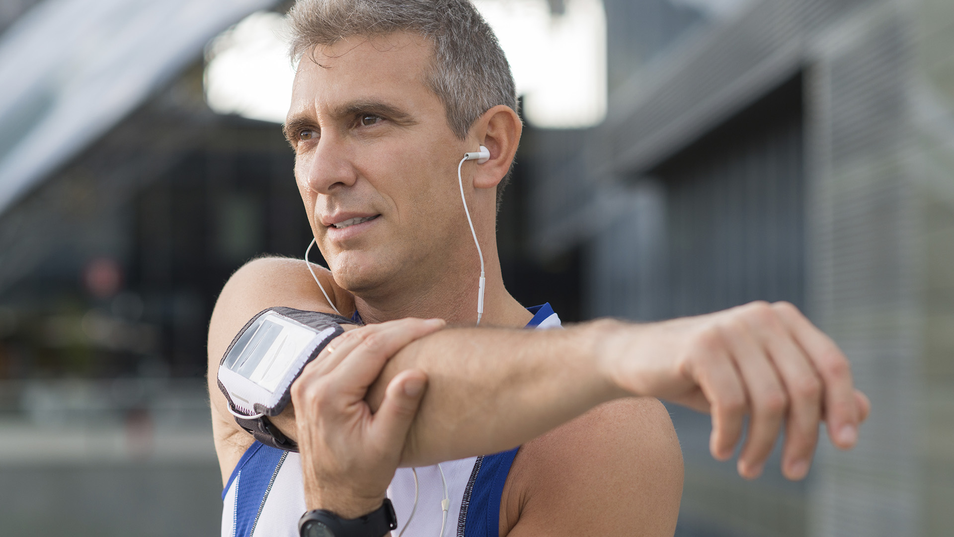 Mature Male Athlete Stretching And Listening To Music Outside