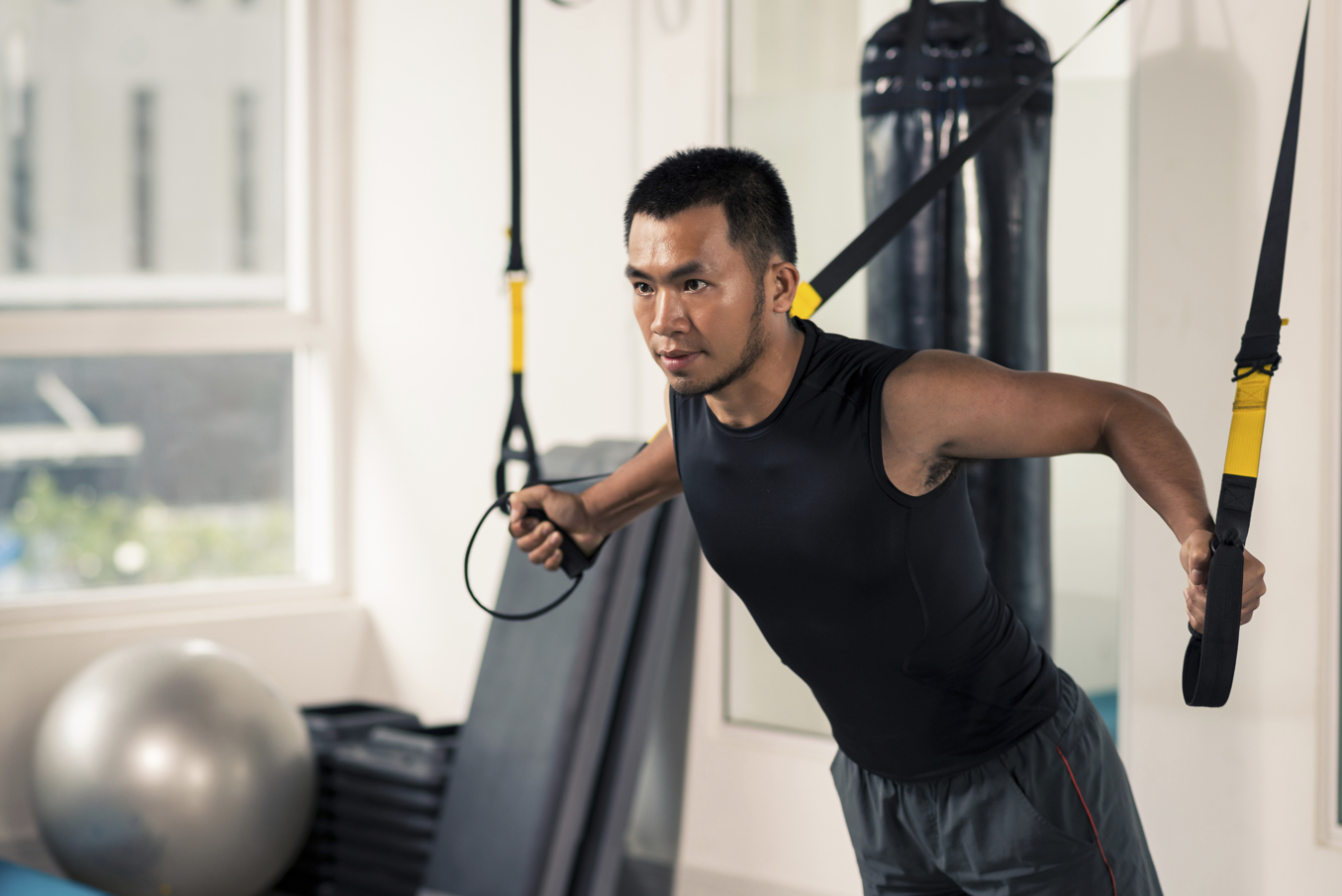 Asian man having fitness TRX training at gym
