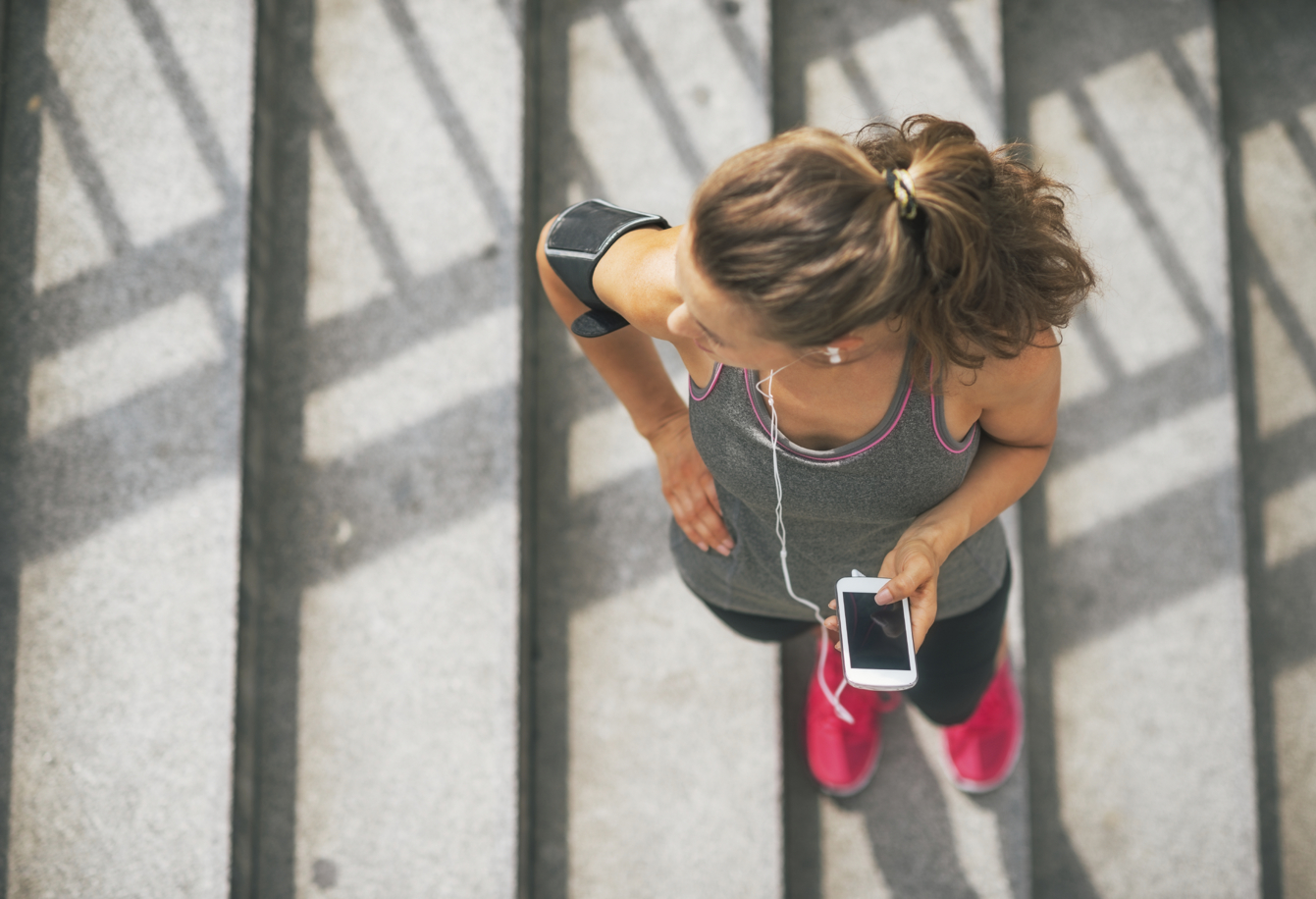 Portrait of fitness young woman with cell phone outdoors in the city
