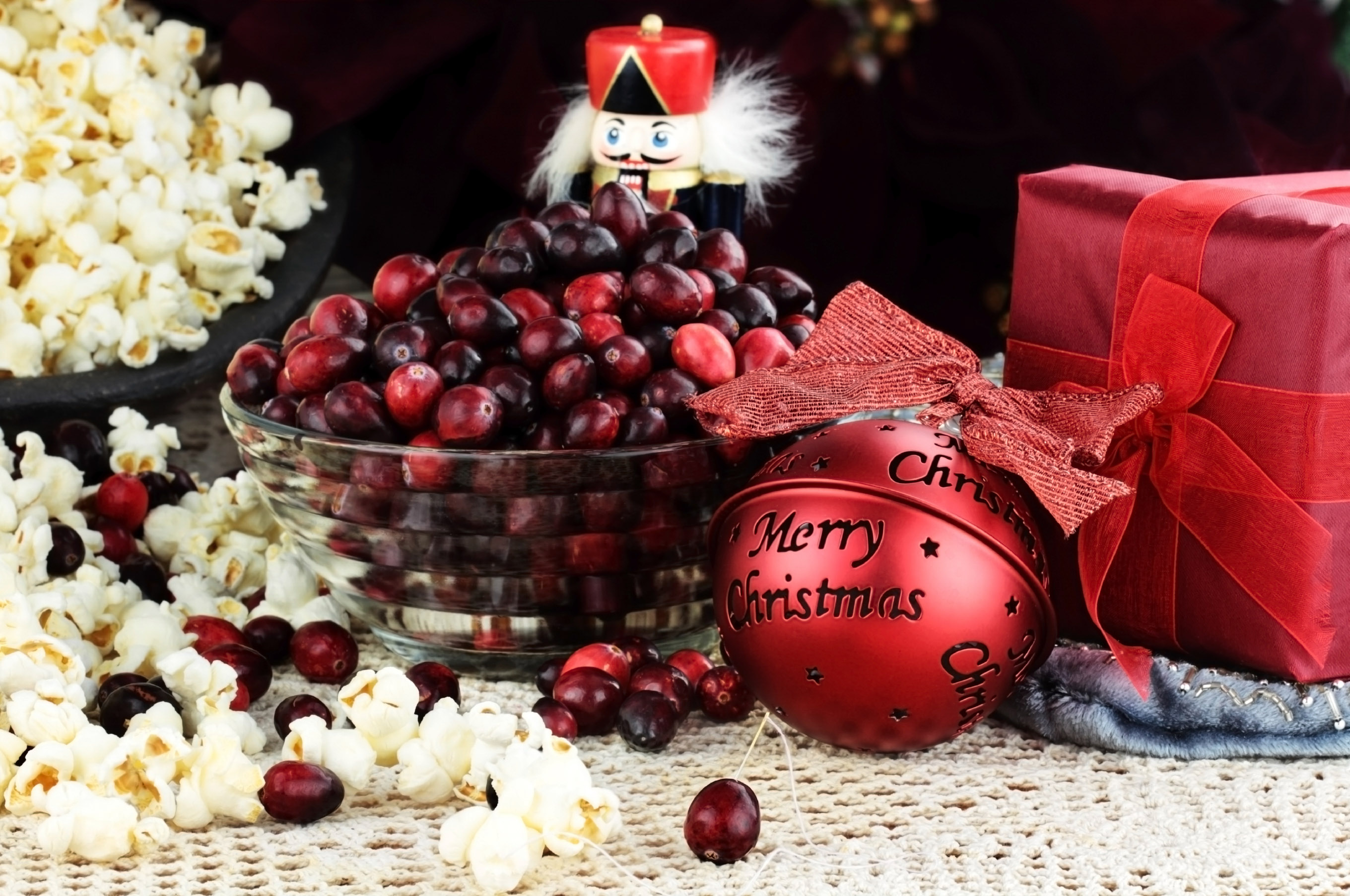 String of popcorn and cranberries with bowl of cranberries, popcorn, gift and ornaments in background. Shallow depth of field.