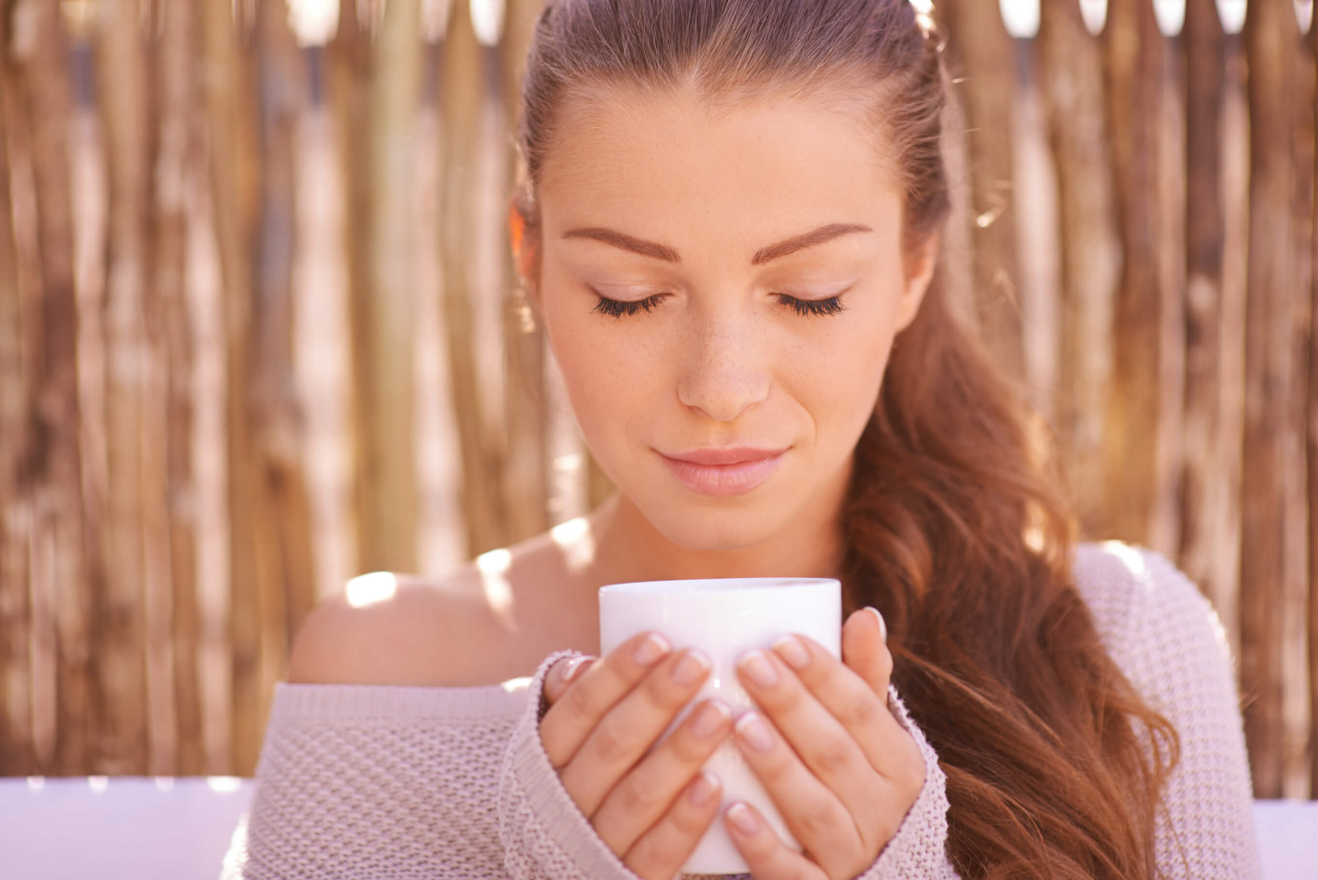 Closeup shot of a gorgeous young woman enjoying a warm drink outdoors