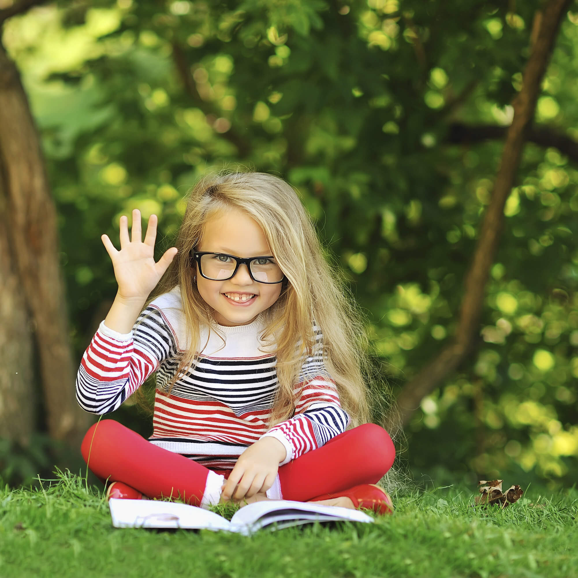 Sweet little girl with a book showing five - outdoors