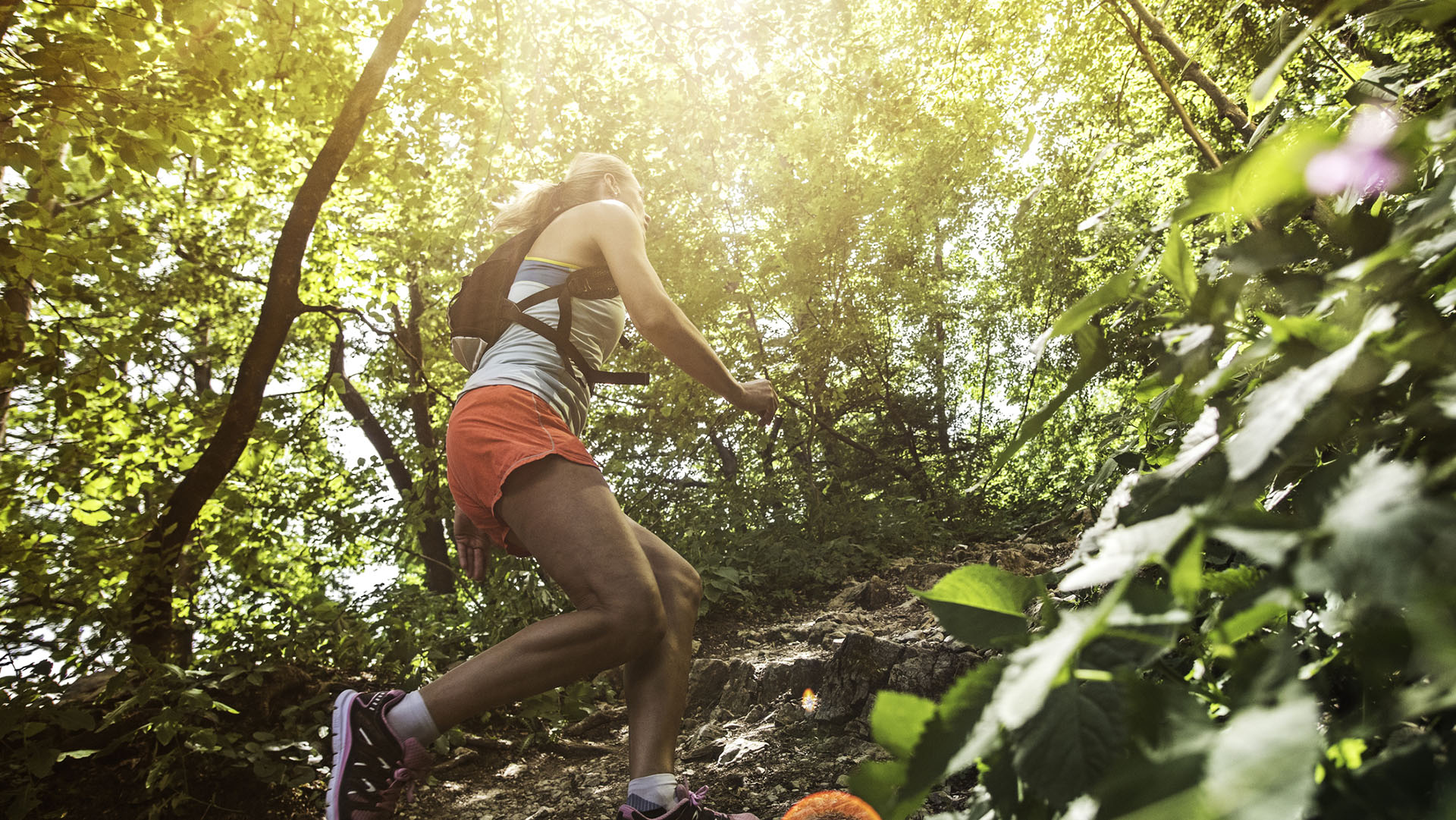 Female runner going uphill on a rocky forest path.