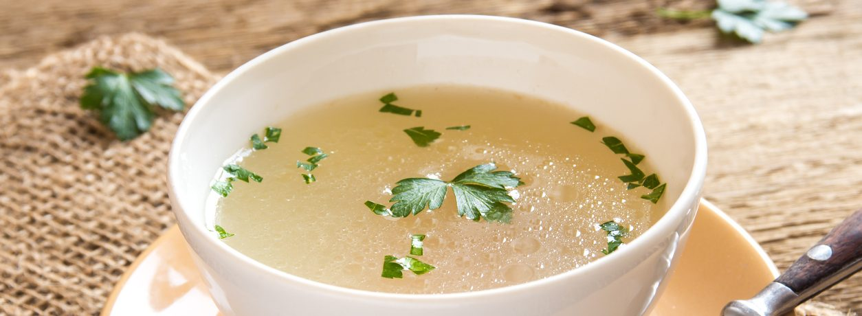 Chicken broth with parsley in white bowl close up