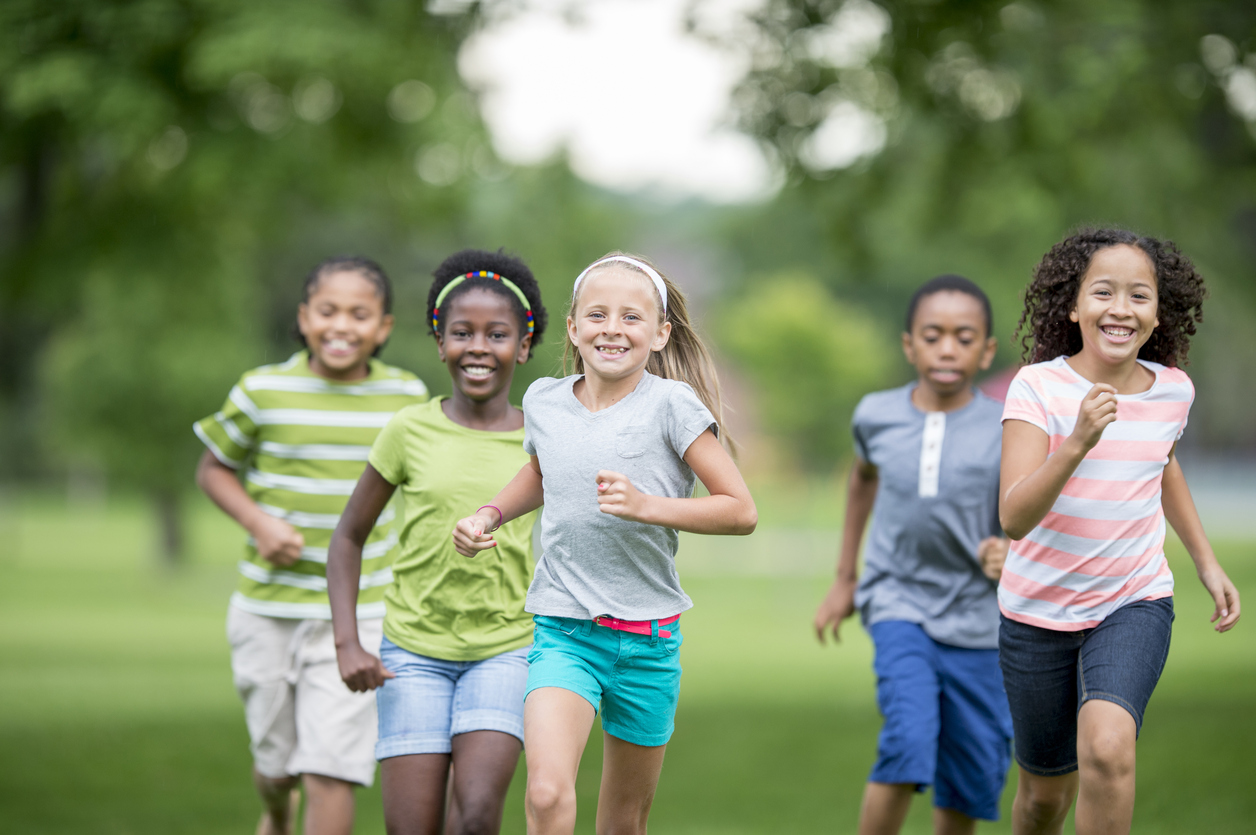 A multi-ethnic group of elementary age students are playing tag at the park during recess. They are happily chasing each other through the grass on a sunny day.