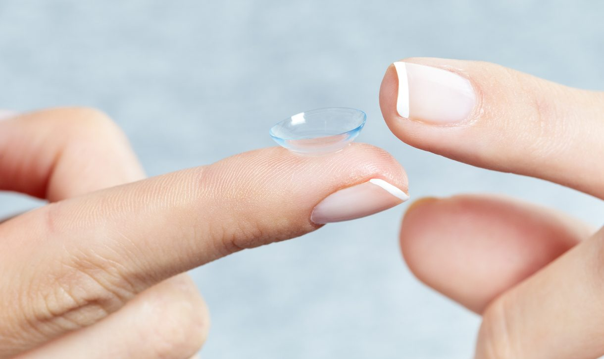 Woman holding a contact lens. Macro studio shot.