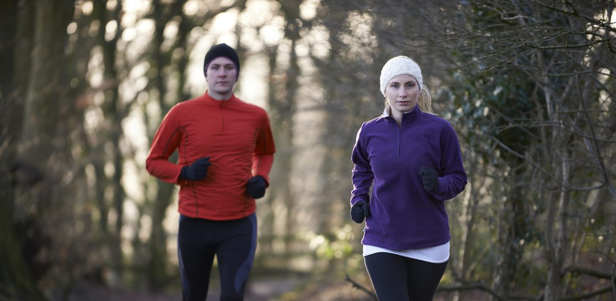Couple On Winter Run Through Woodland
