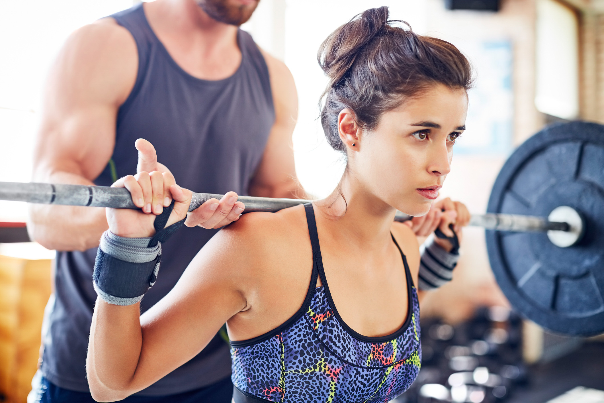 Close-up of young woman lifting barbell while trainer assisting her. She is looking away while exercising. Fitness instructor and female customer are in gym.