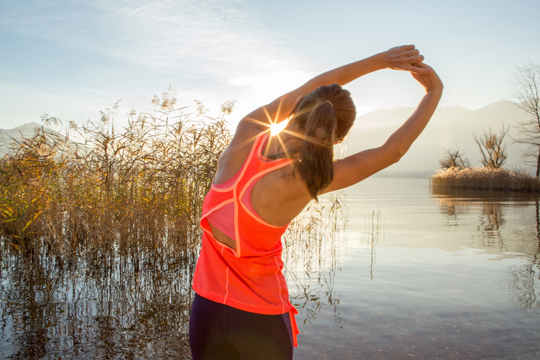 Beautiful and sporty young woman stretching after jogging outdoors. Arms outstretched above head.