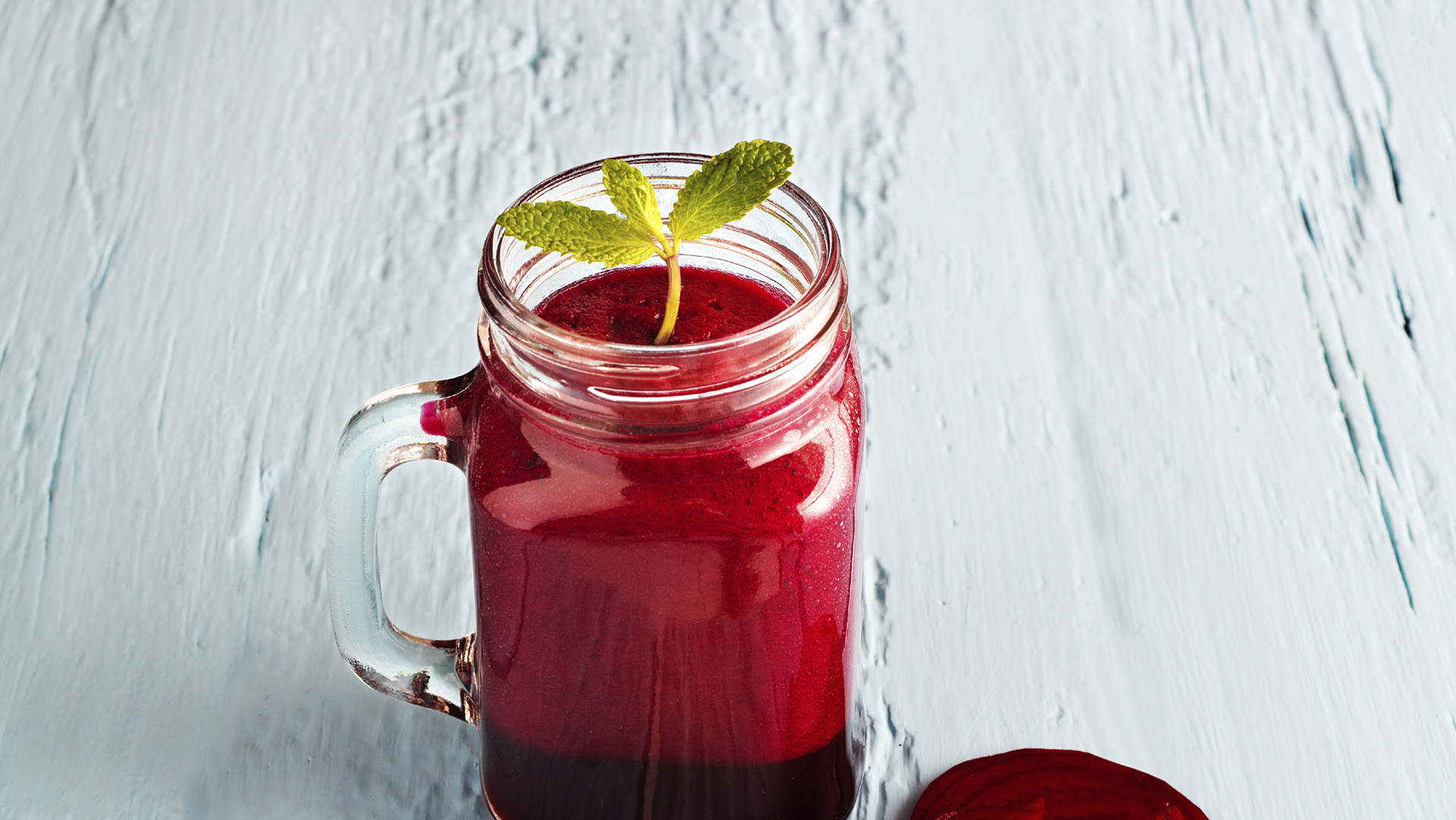 Beetroot smoothie healthy and mint herb on blue wooden backgroun