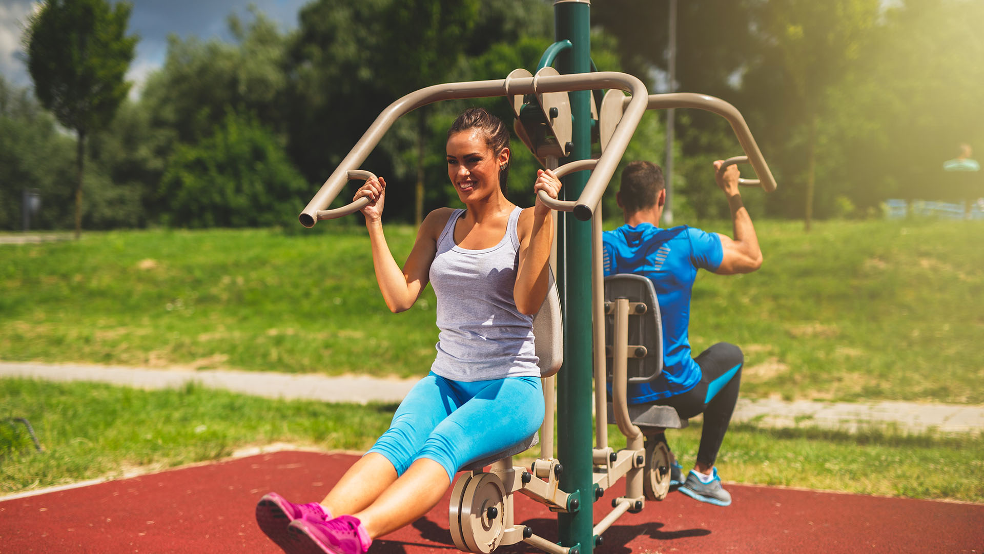 Young couple doing strength exercises on a exercise machine at the outdoor gym.
