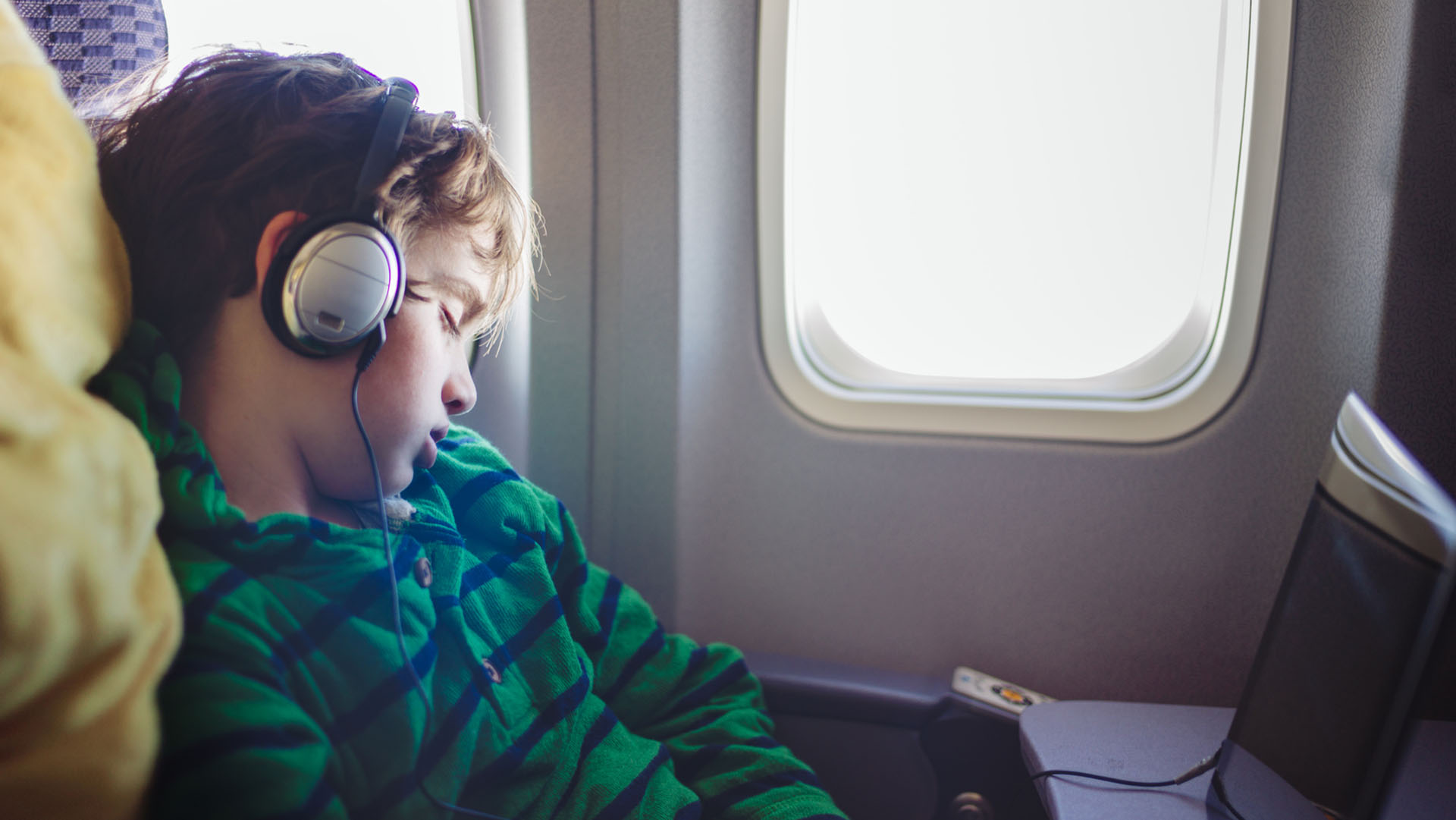 Young boy wearing headphones asleep on an airplane