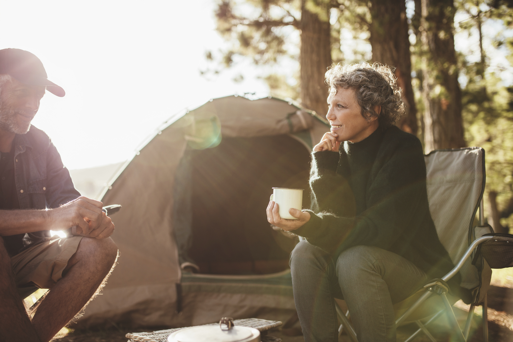 Relaxed couple sitting outside tent while camping nearby lakeside