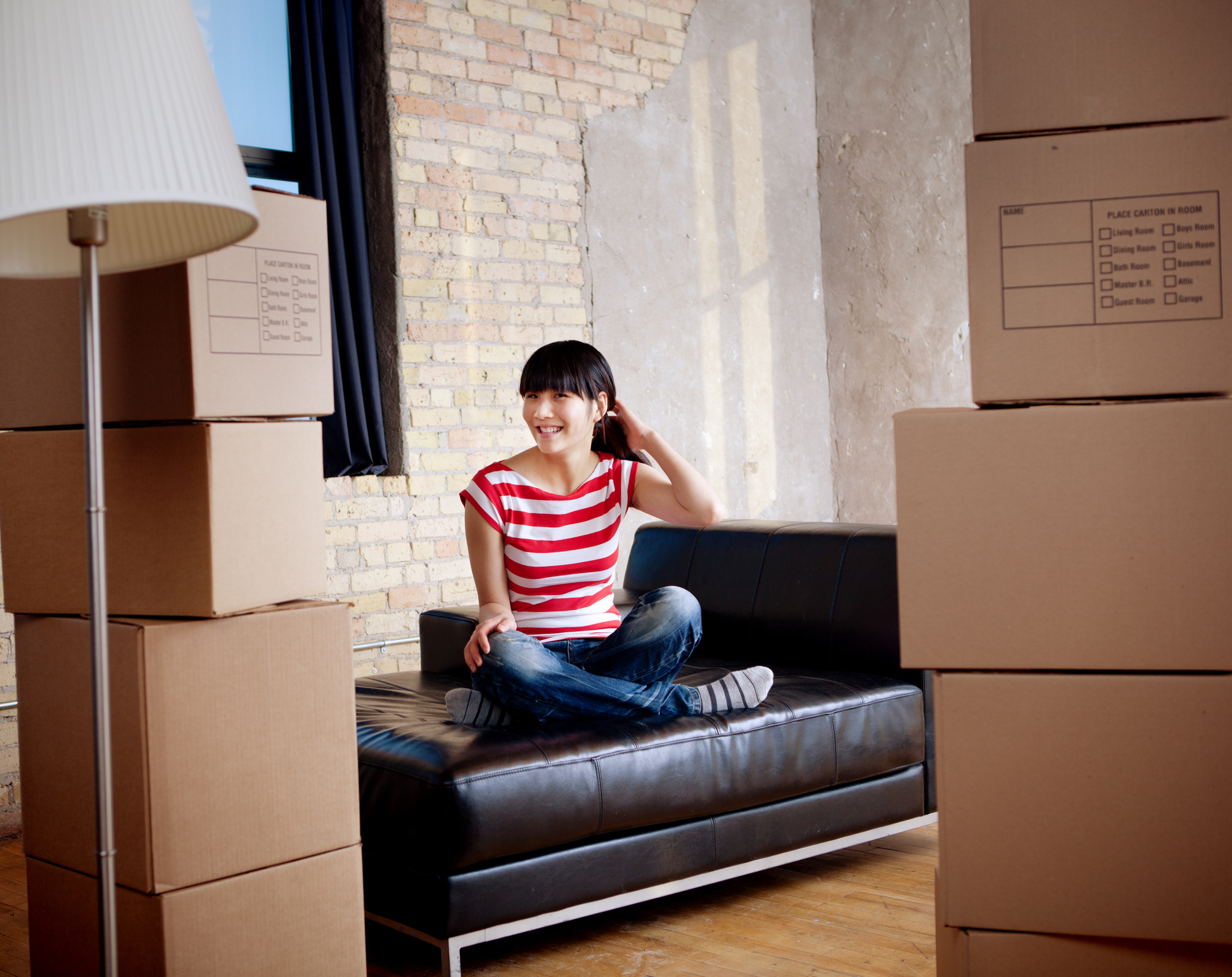 Subject: Horizontal view of a young Asian woman sitting cross legged on a sofa, surrounded by moving boxes. The interior suggests that she is happy that she has just moved into an urban loft apartment or condo.