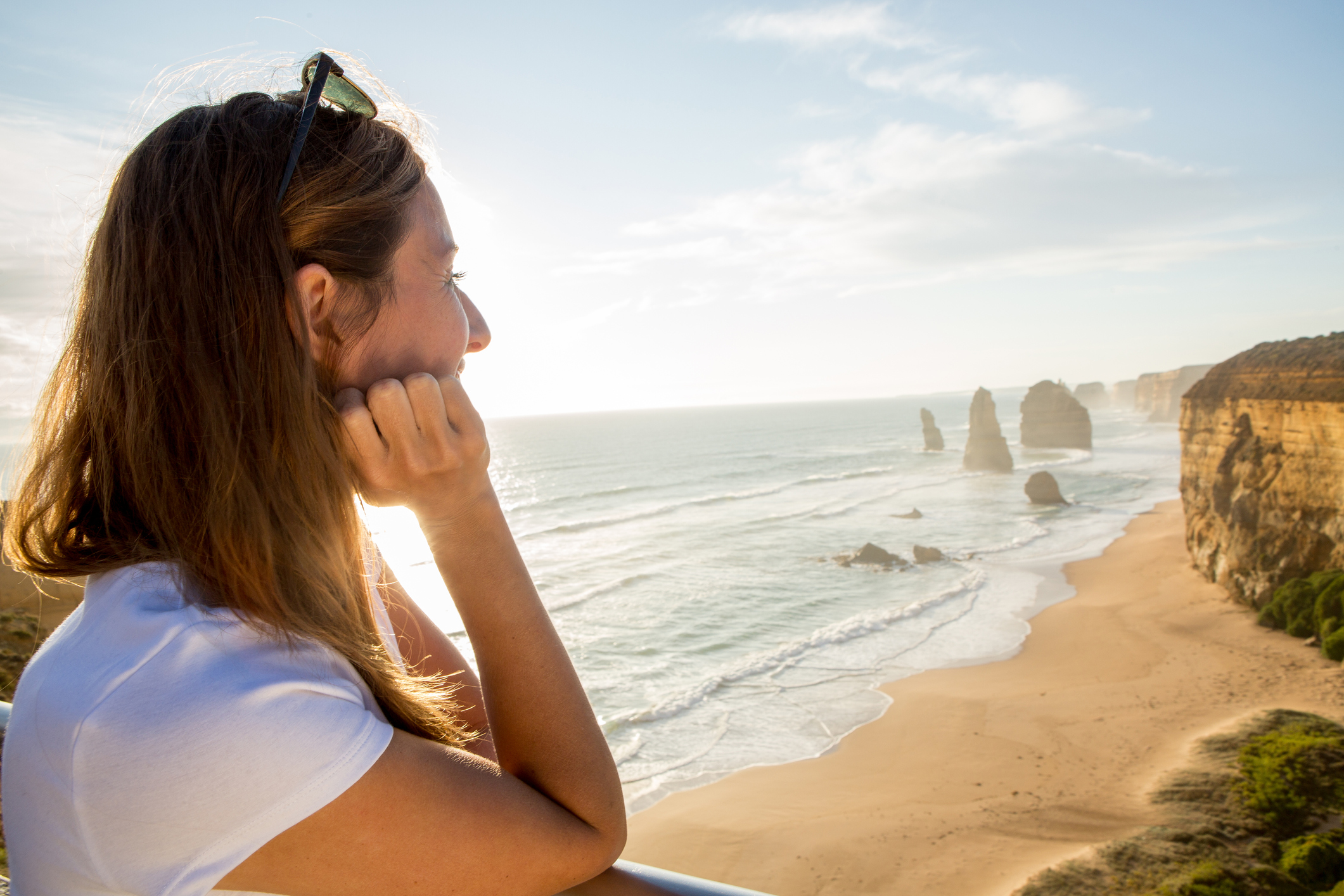 Young woman watches the sunset at the Twelve Apostles sea rocks on the Great Ocean Road in Victoria's state of Australia.