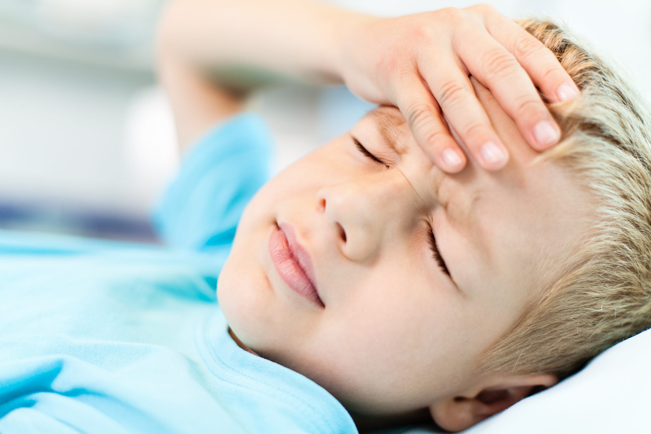 Close-up of little boy with headache, holding his head with his hand.