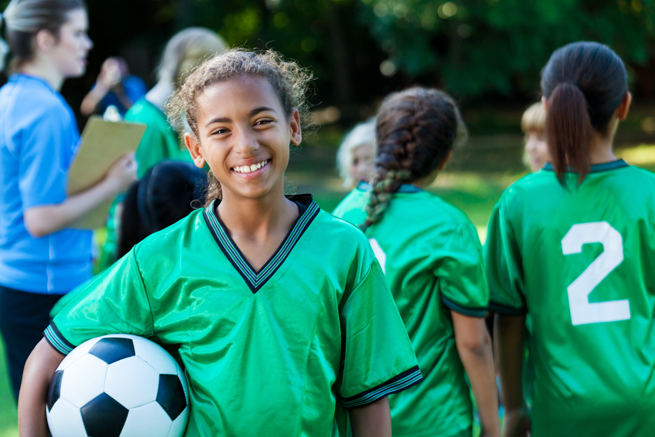 Pretty preteen soccer player smiles at the camera while holding a soccer ball. She is wearing a green jersey. Her team and coach are in the background.