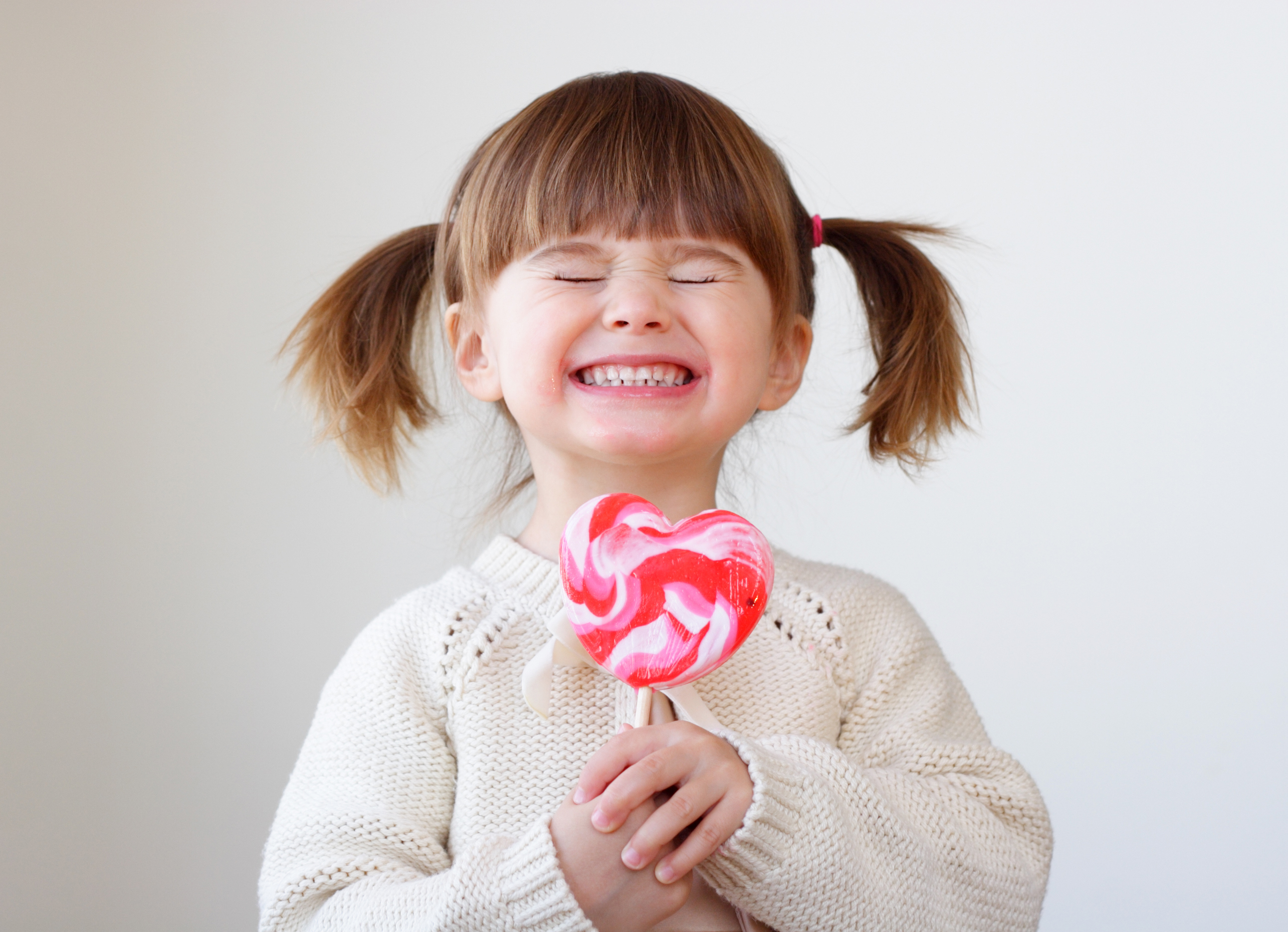 Giddy young girl with a heart-shaped lollipop