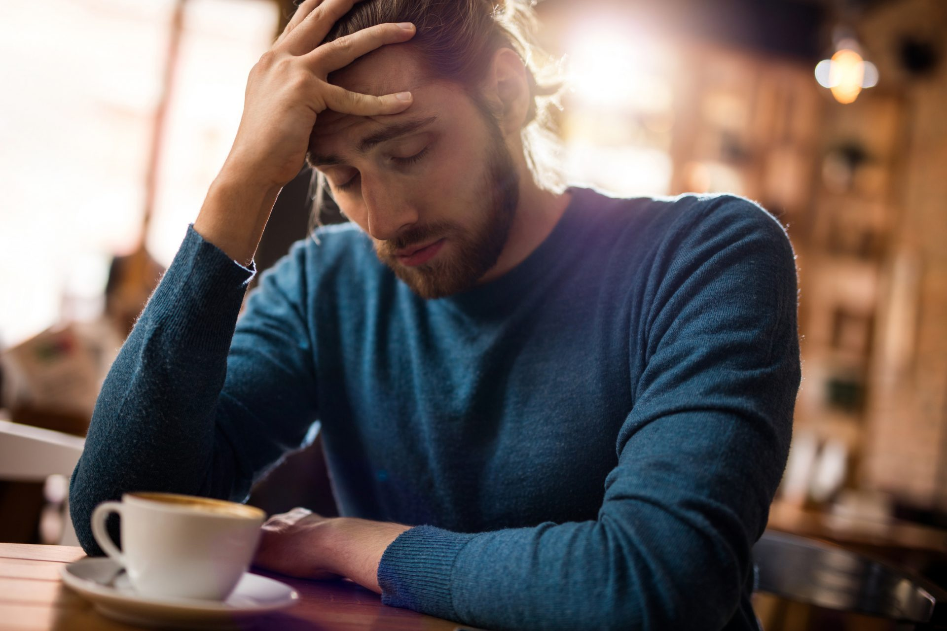 Stressed man holding his head in pain in a cafe.