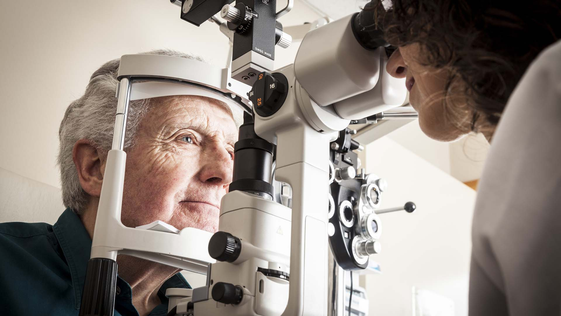 Optometrist giving eye exam to senior patient