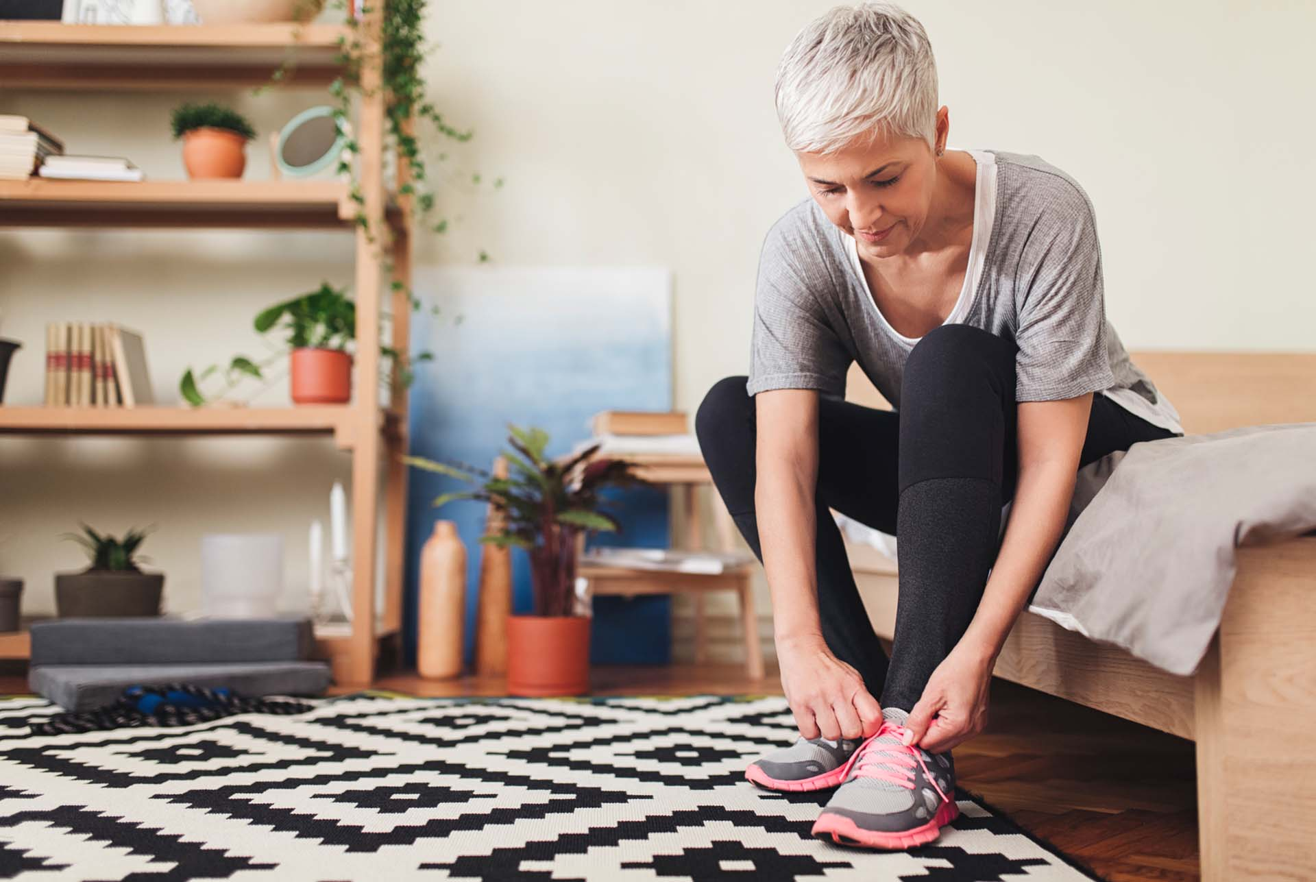 Caucasian senior woman tying the laces on her running sneakers.