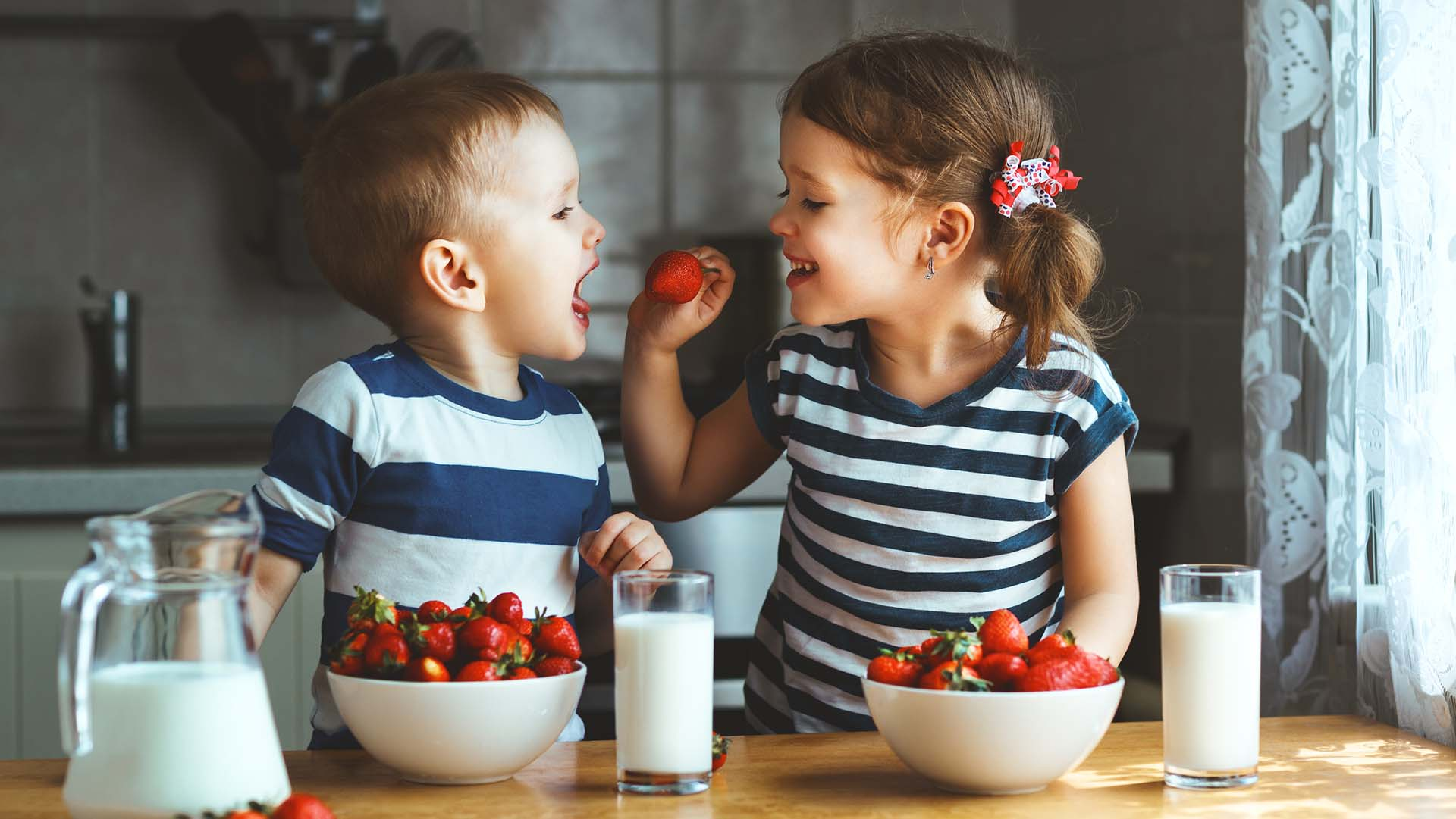 Happy children brother and sister eating strawberries with milk