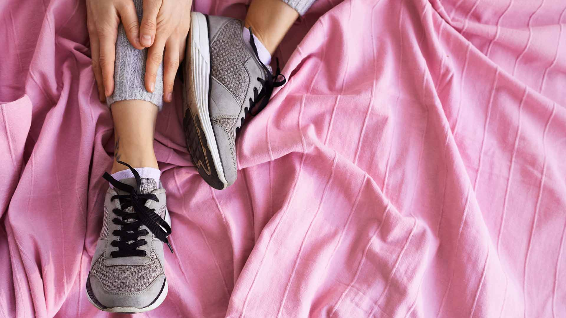 High angle view of female athlete in wool sport pants and sneakers sitting on bed, touching her ankle with both hands and stretching.