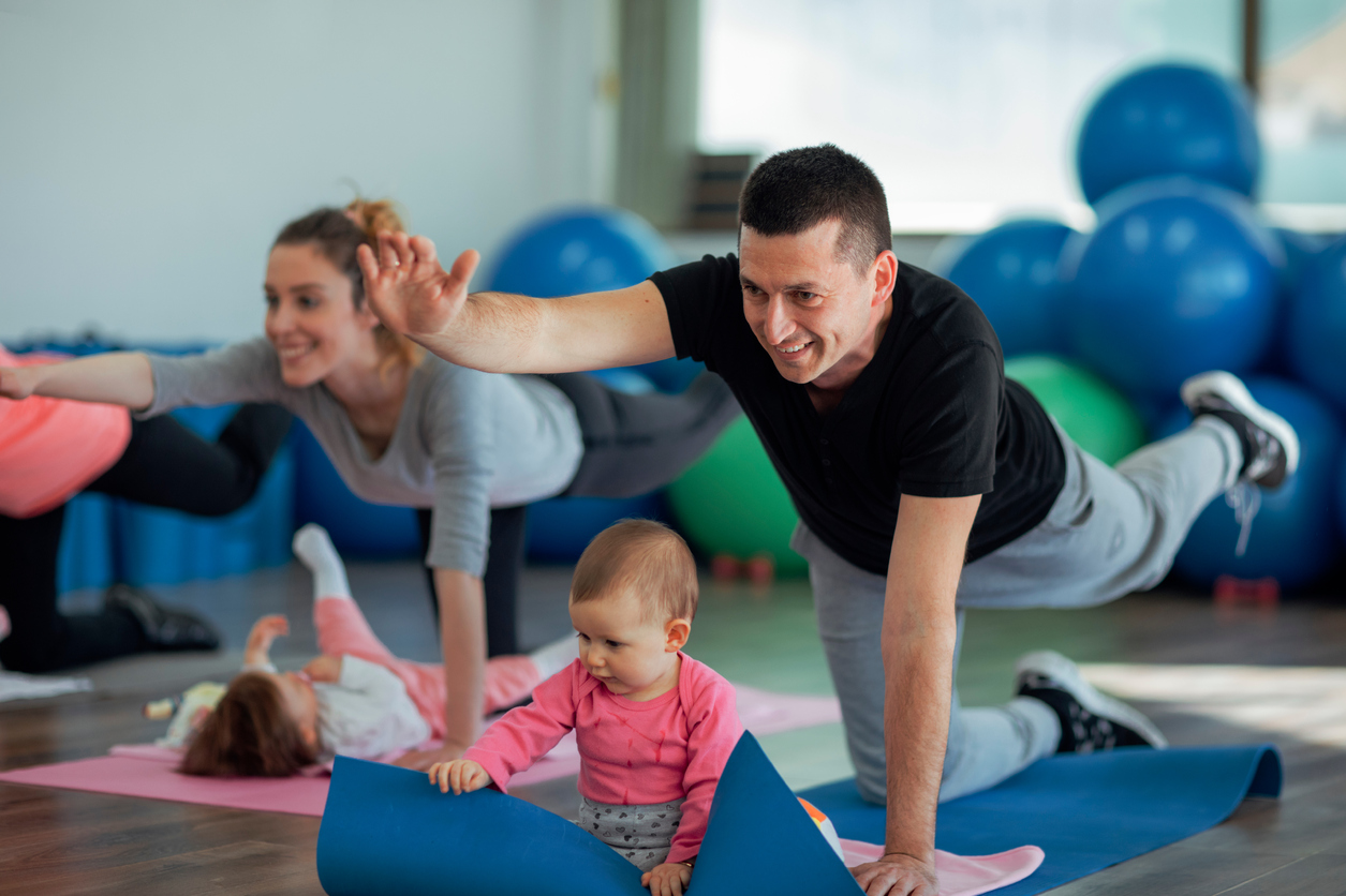 Parents Exercising with Their Babies in a Gym. Selective focus on father exercising with his baby. He is exercising on floor on exercising mat and baby is sitting in front of her dad. He is happy to exercise together with his baby and stay fit.