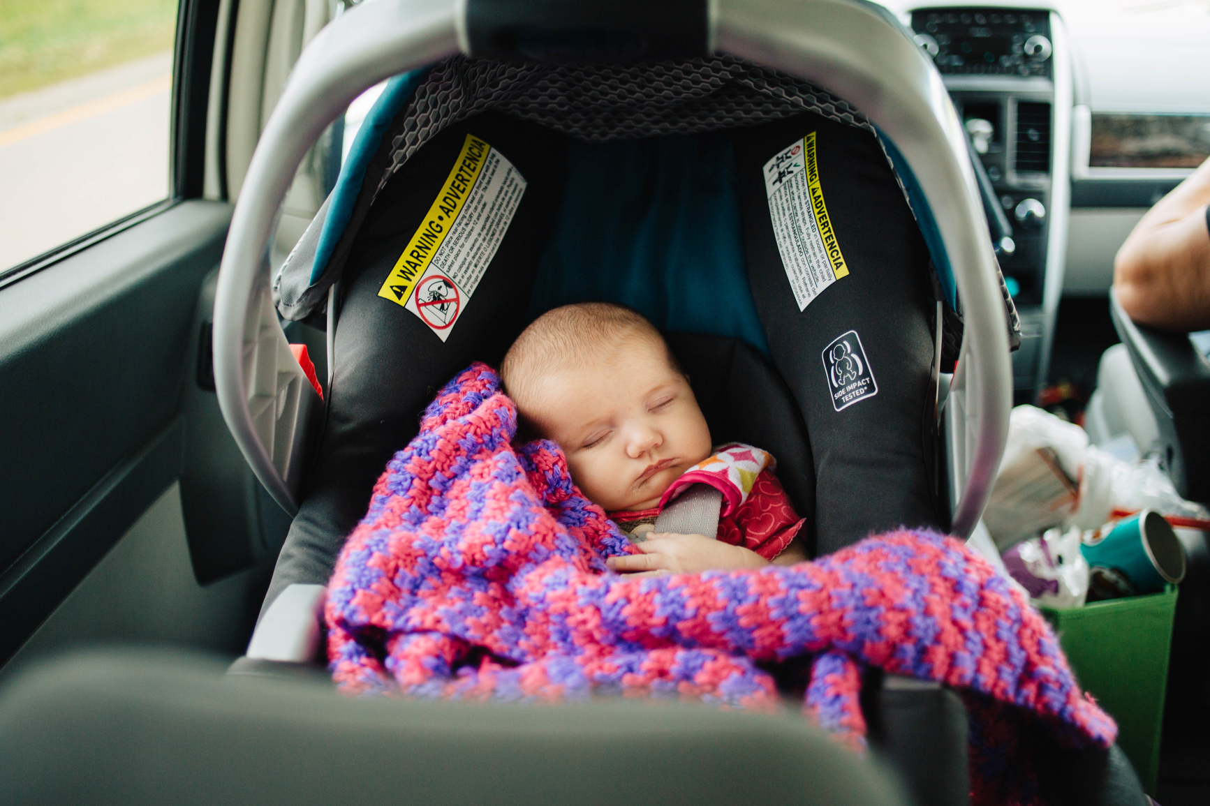 Baby girl sleeping in rear-facing infant seat during a road trip.