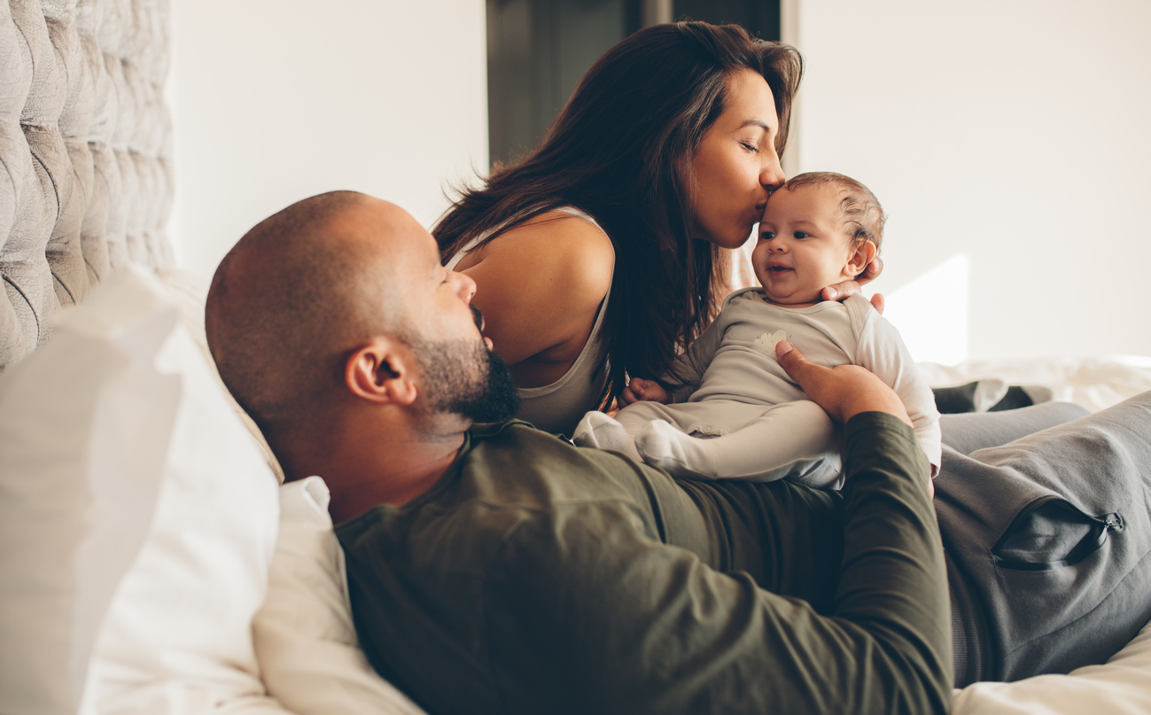 Parents with their newborn baby boy on bed at home. Woman kissing her son sitting with father.