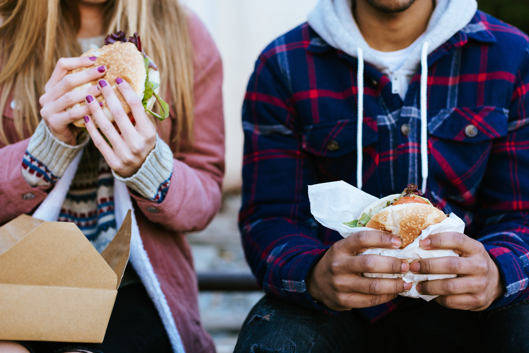 Closeup Of Young Travelers Eating A Burger In A Train Station.